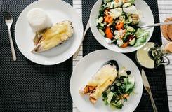 Gegrillte Lachse, Salat und Würzen auf Holztisch Stockfoto