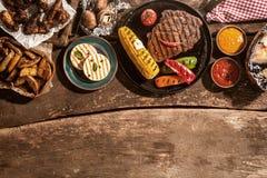 Gegrillte Mahlzeit heraus verbreitet auf rustikalem Holztisch Stockbilder