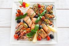 Gegrillte Meeresfrüchtevielzahl auf weißer Platte mit Soße Stockfotografie