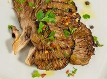 Gegrillte Pilze mit parsely, papricka und wenige Körner des schwarzen Pfeffers Stockfotografie