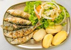 Gegrillte Sardinen mit Mittelmeersalat und gekochten Kartoffeln Lizenzfreies Stockfoto