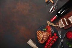 Gegrillte Schweinefleischsteaks mit Flasche Wein, Weinglas, Messer, Gabel, Schwarzbrot, Kirschtomaten und Rosmarin auf rostigem H lizenzfreie stockfotos