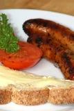 Gegrillte Schweinswürste, Tomate und Toastbrot Stockfotos