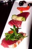 Gegrillte und rohe Thunfischfische auf weißer Platte Stockfotos