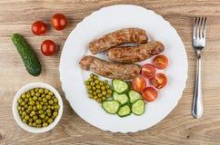 Gegrillte Würste, Gurken, grüne Erbsen, Tomaten in der Platte, gree Lizenzfreie Stockfotos
