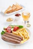 Gegrillte Würste mit Pommes-Frites, Gemüse und Glas Bier Stockbilder