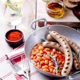 Gegrillte Würste mit Bohnen in der Tomatensauce Stockfoto
