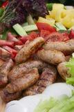 Gegrillte Wurst, frische Kräuter, Tomaten, Zwiebeln Stockbilder