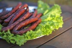 Gegrillte Wurst mit Salatblättern Lizenzfreie Stockbilder