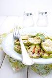 Gegrillte Zucchini in einer weißen Platte mit einer Gabel stockfotos