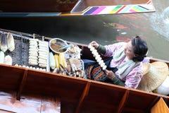 Gegrillter Bananen Verkäufer, der auf ihrem Boot im Kanal an sich hin- und herbewegendem Markt Damnoen Saduak sitzt stockfotos