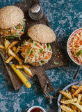 Gegrillter Hühnerburger mit Kohlsalat und Fischrogen auf einem hölzernen Schneidebrett stockfotos