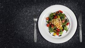 Gegrillter Halloumi-Käse, der mit Olivenöl-Salathexe des Knoblauchs gegossen wurde, grillte Aubergine, Kirschtomaten, schwarze Ol lizenzfreie stockfotografie