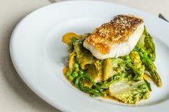 Gegrillter Kabeljau mit Spargel und Salat verlässt auf einer weißen Platte Stockbild