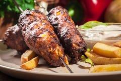 Gegrillter Kebab diente mit gebratenen Chips und Salat Stockfoto