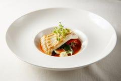 Gegrillter Steinbutt, tabouli, Gemüsepaprikasoße und Sommergemüse Weißer Teller Stockfoto