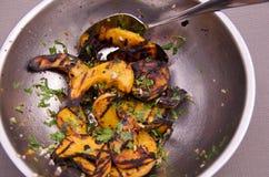 Gegrillter Winterkürbissalat in einer Edelstahlschüssel mit Umhüllungslöffel Stockfoto