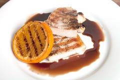 Gegrilltes Fleisch mit orange Soße auf einer weißen Platte Stockfoto