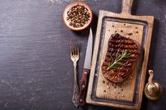 Gegrilltes Fleisch mit Rosmarin auf hölzernem Brett lizenzfreies stockbild