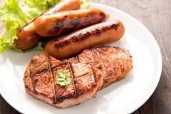 Gegrilltes Fleisch, Würste und Gemüse auf Tellerabschluß oben Stockbild