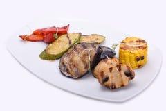 gegrilltes Gemüse auf einer weißen Platte - Aubergine, Zucchini, Champignons, Mais und roter Gemüsepaprika stockbild
