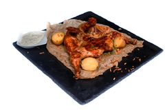Gegrilltes Huhn mit Kartoffeln und weißer Soße auf einem schwarzen Brett auf lokalisiertem weißem Hintergrund lizenzfreie stockfotos