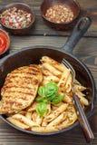 Gegrilltes Huhn und Penne-Teigwaren mit Gewürzen und Basilikum Stockfoto