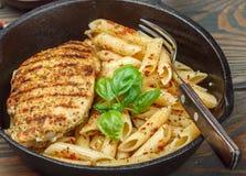 Gegrilltes Huhn und Penne-Teigwaren mit Gewürzen und Basilikum Lizenzfreies Stockfoto