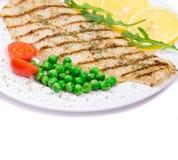 Gegrilltes Lachssteak diente von den Erbsen und von den Tomaten Stockfotos