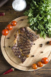 Gegrilltes Rindfleischsteak auf hölzernem Brett auf hölzernem Hintergrund lizenzfreies stockfoto