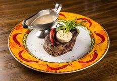 Gegrilltes Rindfleischsteak mit Käse- und Pfeffersoße auf Platte stockbild