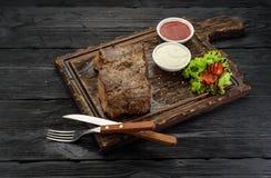 Gegrilltes Rindfleischsteak mit Soßen auf einem Brett Dunkler Holztisch Stockbilder