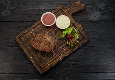 Gegrilltes Rindfleischsteak mit Soßen auf einem Brett Dunkler Holztisch Stockfotografie