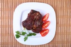 Gegrilltes Rindfleischsteak mit Tomate und heiße asiatische Paprikaknoblauchsoße auf Platte auf hölzernem Hintergrund Lizenzfreies Stockfoto
