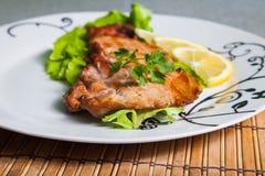 Gegrilltes Schweinefleisch mit Salat und Zitrone lizenzfreie stockfotos