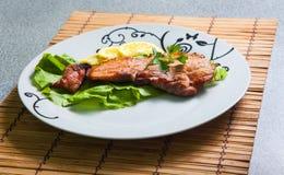 Gegrilltes Schweinefleisch mit Zitrone und Salat lizenzfreie stockbilder