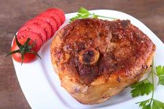 Gegrilltes Schweinekotelett mit geschnittener Tomate und Soße auf Holztisch Stockfotos