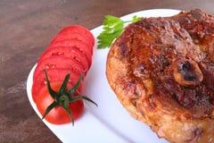 Gegrilltes Schweinekotelett mit geschnittener Tomate und Soße auf Holztisch Lizenzfreies Stockbild