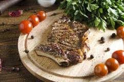 Gegrilltes Steak auf hölzernem Brett auf hölzernem Hintergrund Stockbild