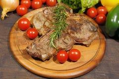 Gegrilltes Steak des förmigen Knochens mit Rosmarintomaten, Paprikazwiebeln und lizenzfreies stockbild