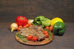 Gegrilltes Steak des förmigen Knochens mit Rosmarintomaten, Paprikazwiebeln und lizenzfreies stockfoto