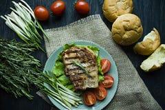 Gegrilltes Steak diente auf einer Platte, verziert mit Gew?rzen f?r Fleisch, Rosmarin, Gr?ns und Gem?se auf einem dunklen h?lzern lizenzfreie stockfotos