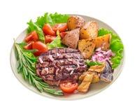 Gegrilltes Steak mit dem Gemüse und Rosmarin lokalisiert lizenzfreie stockbilder