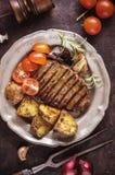 Gegrilltes Steak mit geschnittener Kartoffel und den Tomaten vertikal Stockfotos