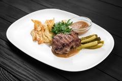 Gegrilltes Steak mit Kartoffeln und Soße auf weißer Platte Stockbild