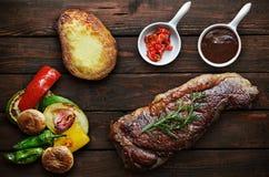 Gegrilltes Steakfleisch mit roten Pfeffern auf Tafelhintergrund Stockbild