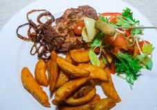 Gegrilltes T-Bone-Steak würzte mit Gewürzen und frischen Kräutern frische Tomate, Bratenkartoffeln und glühende Paprikapfeffer Stockbild