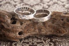 Gehämmerte Ringe auf Treibholz und Papier Lizenzfreie Stockfotos