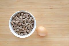 Gehackt von gekochter Schweinefleischleber in den weißen Schüsseln auf hölzernem Brett mit Ei stockfoto
