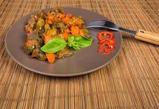 Gehackte Auberginen gedünstet mit anderem Gemüse auf braunem Teller stockfotos